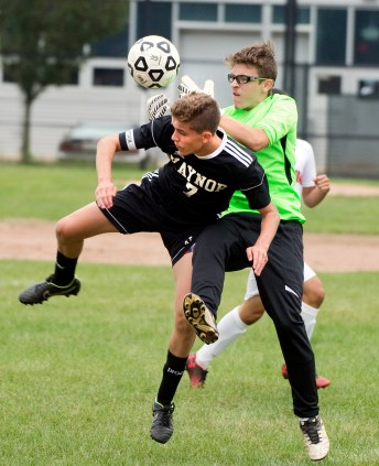 Kaynor Tech's Matheus Silva (7) tries to get a piece of the ball as Goodwin Tech's Kenny Hemenway (1) comes out for the save during their game Monday at Kaynor Tech High School in Waterbury. Jim Shannon Republican American