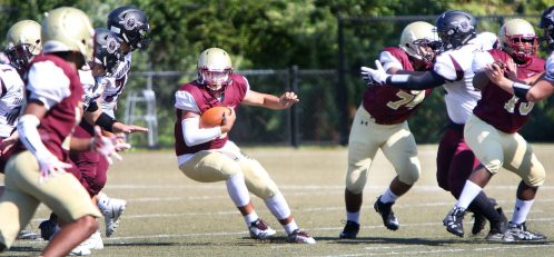 QB #11 Alex Gonzalez of Sacred Heart/Kaynor finds a hole in the line for yardage against Torrington defends during the 2nd quarter of NVL football action at Municipal Stadium in Waterbury Saturday. Steven Valenti Republican-American