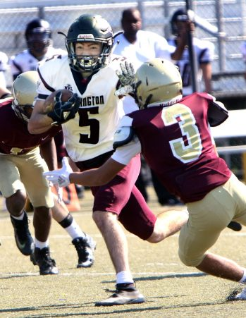 #5 Jacob Coleman of Torrington runs for yardage as #3 Jon Irizarry of Sacred Heart/Kaynor defends during the 1st quarter of NVL football action at Municipal Stadium in Waterbury Saturday. Steven Valenti Republican-American