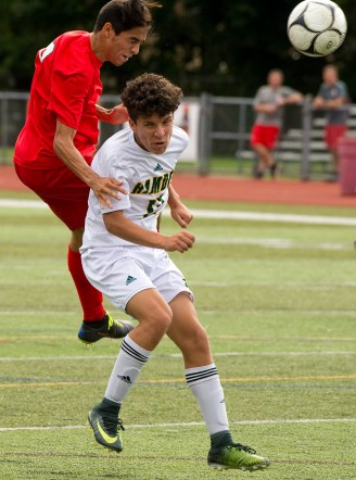 Cheshire's Denys Fuentes (9) gets a head on the ball over Hamden's Joshua Venditto (17) battle for the ball during their game Wednesday at Cheshire High School. Jim Shannon Republican American