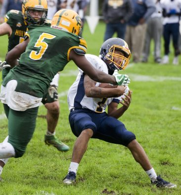 Kennedy's Matt Torres (1) is sacked by Kennedy's Marcus Payne (5) during their NVL game Saturday at Holy Cross High School. Jim Shannon Republican American