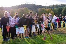 Maegan Desmarais of Thomaston heads to the finish line as Keegan Daigle of Thomaston cheers her on during the BL Boys and Girls Cross Country Championships at Black Rock State Park in Watertown on Friday. Bill Shettle Republican-American