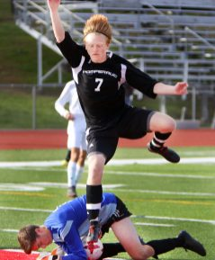 #7 Jack OÕBrien of Pomperaug High makes a shot on goal then jumps to avoid goalie #1 John Hoeing of Joel Barlow who makes the save during Soccer action in Southbury Friday. Steven Valenti Republican-American