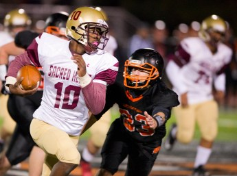 Sacred Heart-Kaynor Tech's Saigon McIntosh (10) gets past Watertown's Anthony Velardi (33) for a first down during their game Friday at Watertown High School. Jim Shannon Republican American