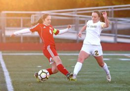 Wolcott High School's Bella Piacentini and Holy Cross High School's McKenna Ellsworth battle for the ball as the sun goes down during the NVL Girls' Soccer Tournament semi-final girls varsity soccer game in Watertown on Tuesday. Emily J. Reynolds. Republican-American