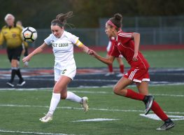 Holy Cross High School's McKenna Ellsworth keeps her eye on the ball in front of Wolcott High School's Ella Vaughn during the NVL Girls' Soccer Tournament semi-final girls varsity soccer game in Watertown on Tuesday. Emily J. Reynolds. Republican-American