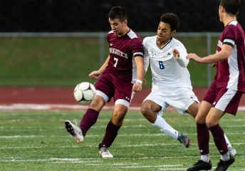 Naugatuck's Thomas Martins #7 passes the ball with Newtown's Jalen Minter #6 defending during the first round of the CIAC Class LL boys' soccer tournament between #22 Newtown and #11 Naugatuck at Naugatuck High School in Naugatuck on Tuesday. Naugatuck beat Newtown 1-0 and advances to the next round on Thursday. Bill Shettle Republican-American