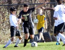 #2 Jason Claiborn of Woodland tries to clear a ball down field as #12 Frandi Aguilar of Aerospace defends during CIAC Class M soccer action in Beacon Falls Wednesday. Steven Valenti Republican-American