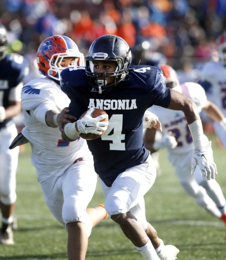 Ansonia's Tajik Bagley (4) carries the ball ahead of Bloomfield's Ventine Richardson during their Class S state final matchup in New Britain on Saturday. Ansonia would go onto lose, 31-20. Christopher Massa Republican-American