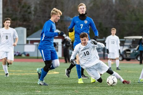 Pomperaug's Zachary Hoedl #10 gets tripped up by Glastonbury's Zachary Gardner #23 left, as Glastonbury's Alec Hughes #7 looks on during a Boys Soccer Class L Semifinal game between Glastonbury and Pomperaug at Veterans Memorial Stadium at Willowbrook Park in New Britain on Wednesday. Bill Shettle Republican-American