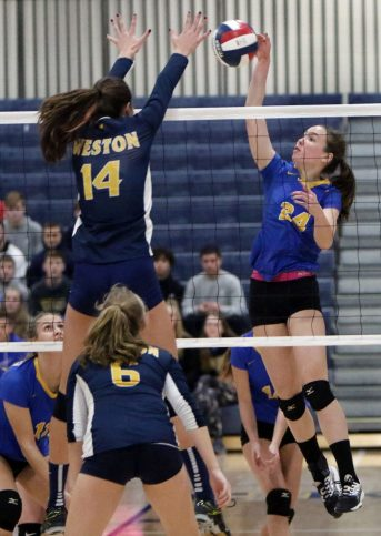#24 Faith Rousseau of Seymour High blocks a shot from #14 Katherine Anderson of Weston during the CIAC Class M volleyball championship game in East Haven Saturday. Steven Valenti Republican-American