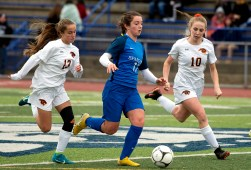 Lewis Mills' Madison Hallet (17) runs the ball past Plainfield's Karley Belsilie (13) and Cassie Carelson (10) during their Class M soccer championship game Sunday at West Haven High School. Jim Shannon Republican American