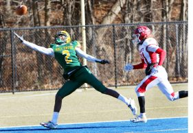 #2 Qaron Brown of Holy Cross reaches for a pass as #21 Matthew Olmstead of Wolcott defends during 1st quarter football action in Waterbury Friday. Steven Valenti Republican-American
