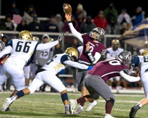 Naugatuck's John Mezzo (12) gets hit by Platt's Jasiah Cooper (35) as he throws a pass during their Class L quarterfinal game Tuesday at Naugatuck High School. Jim Shannon Republican American