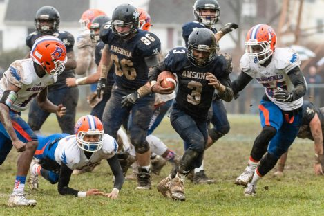 Ansonia running back Shykeem Harmon #3 runs with ball up the middle past the diving Bloomfield's Antwan Tinsley #18 and Bloomfield's Jaden Saulter #55, right, during the Class S Semi-final game between Bloomfield and Ansonia at Ansonia High School in Ansonia on Sunday. Bloomfield held on to beat Ansonia 26-19 and advances to the Class S Championship game next week. Bill Shettle Republican-American
