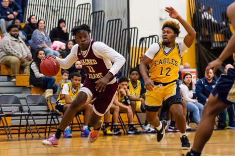 Sacred Heart forward Jamaal Waters #11 drives to the basket past Kennedy defender Dimitri Calle #12 during the annual Waterbury Boys Basketball Jamboree at Kennedy High School in Waterbury on Sunday. Bill Shettle Republican-American