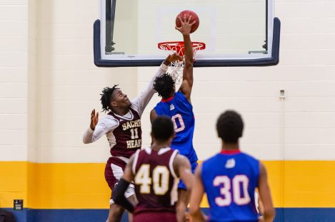 Crosby center Kerwin Prince #0 goes up high down the middle for a dunk against Sacred Heart's Jamaal Waters #11during the annual Waterbury Boys Basketball Jamboree at Kennedy High School in Waterbury on Sunday. Bill Shettle Republican-American