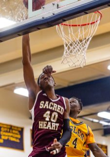 Sacred Heart's Omar Rowe #40 gets fouled hard by Kennedy's Jay Turner #24, going in for a layup during the annual Waterbury Boys Basketball Jamboree at Kennedy High School in Waterbury on Sunday. Bill Shettle Republican-American