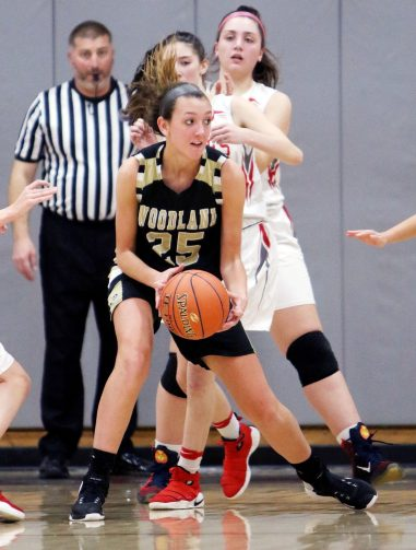#25 Ava DeLucia of Woodland High looks to pass under pressure against Wolcott High during 1st quarter NVL basketball action in Wolcott Monday. Steven Valenti Republican-American