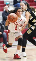 #1 Emiah Soto of Wolcott High drives to the hoop as #21 Hana Bojka of Woodland High defends during 1st quarter NVL basketball action in Wolcott Monday. Steven Valenti Republican-American