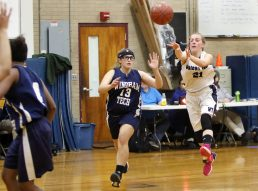 #21 Katie Benedict of Oliver Wolcott Tech. passes inside as #13 Brianna Macha of Windham Tech. defends during basketball action in Torrington Monday. Steven Valenti Republican-American