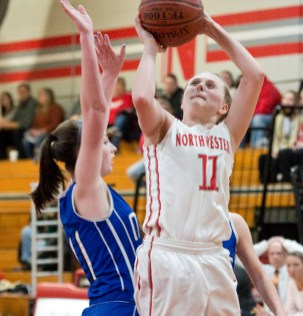 Northwestern's Skylar Dimartino (11) puts up a shot over Lewis Mills' Emily Hunt (11) during their game Tuesday at Northwestern Regional High School. Jim Shannon Republican American