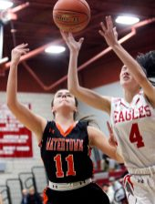 #11 Allie Mazzarella of Watertown High and #4 Kalani Rodriguez of Wolcott High reach for the rebound during basketball action in Wolcott Thursday. Steven Valenti Republican-American