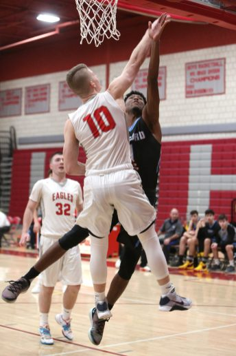 Oxford High School's Charles Flowers goes up for a shot in front of Wolcott High School's Jeffrey Nicol during the varsity basketball game in Wolcott on Wednesday night. Emily J. Reynolds. Republican-American