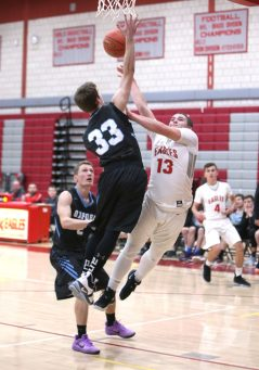Wolcott High School's Christopher Harris goes up for a shot over Oxford High School's Hunter Keller during the varsity basketball game in Wolcott on Wednesday night. Emily J. Reynolds. Republican-American