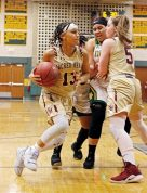 Sacred Heart's Mikayla Mobley (#13) plays off a pic set by teammate Paige Carroll (#5) against Holy Cross' Ja'Ln Waters (#25) Friday night during NVL action at Holy Cross High School. Michael Kabelka / Republican-American