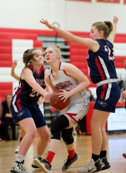 Pomperaug's Maggie Lee (33) drives to the basket between New Fairfield's Abby Flanagan (20) and Kerrigan Quinn (24) during their SWC game Tuesday at Pomperaug High School. Jim Shannon Republican American