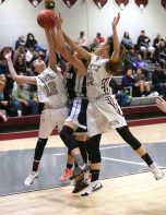 Naugatuck High School's Kaylee Jackson, left, and Sarah Macary battle Ansonia High School's Natasha Rivera for a rebound during the girls varsity basketball game in Waterbury on Wednesday night. Emily J. Reynolds. Republican-American