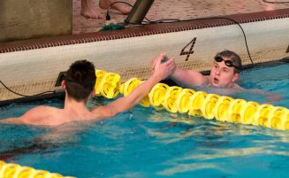 Holy Cross' Derek Fantano, right, shakes hands with Woodland's Greg Aldrich after they competed in the 200 individual medley during their meet Friday at the John Reardon Pool at Kennedy High School in Waterbury. Jim Shannon Republican American