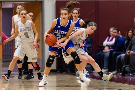 Naugatuck's Julia Kropo #32 reaches in trying to steal the ball away from Bristol Eastern's Sage Scarritt #25, during a second round tournament game in the Girls Class L Basketball Championships between Bristol Eastern and Naugatuck at Naugatuck High School in Naugatuck on Thursday. Bill Shettle Republican-American