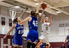 Naugatuck's Sarah Wisniewski #0 puts a running one hander as she drives down the lane against Bristol Eastern's Sage Scarritt #25 and Avery Arbuckle #42, during a second round tournament game in the Girls Class L Basketball Championships between Bristol Eastern and Naugatuck at Naugatuck High School in Naugatuck on Thursday. Bill Shettle Republican-American