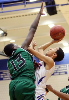 -#3 Jordan Santos of Crosby High puts up a shot over #13 Shariff Bilewu of Wilby High during NVL basketball action in Waterbury Monday. Steven Valenti Republican-American