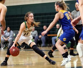 #11 Hannah Brown of Holy Cross High sets up a play as #10 Megan Condo of Seymour High defends during the NVL girlÕs basketball tournament in Waterbury Saturday. Steven Valenti Republican-American