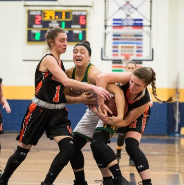 Holy Cross' Jenna Mowad (12) fights to keep the ball with Watertown's Cayla D'Elia (1) and Alyssa Santangeli (14) during their NVL semi-final game Monday at Kennedy High School in Waterbury. Jim Shannon Republican American