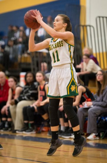 Holy Cross' Hannah Brown (11) hits a three-point shot during their NVL semi-final game against Watertown Monday at Kennedy High School in Waterbury. Brown scored 12 in their 48-32 win over the Indians. Jim Shannon Republican American
