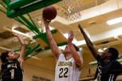 Holy Cross' Jack Greene #22 goes to the basket against WCA defenders Jonathan Edwards #1, left, and Lawrence Lazaro #13, during the boys NVL Conference Tournament between WCA and Holy Cross at Wilby High School in Waterbury on Saturday. Bill Shettle Republican-American