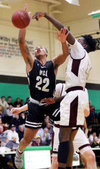 #22 Marquan Watson of Waterbury Career Academy gets fouled by #11 Jamaal Waters of Sacred Heart High during NVL semi final basketball action in Waterbury Monday. Steven Valenti Republican-American
