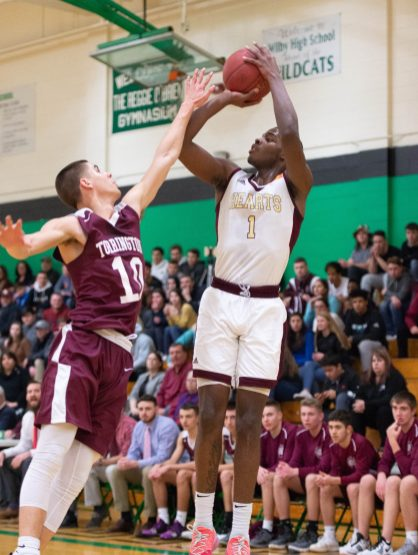 Sacred Hearts' Nate Tabor (1) gets fouled by Torrington's Joel Villanueva (10) while putting up a shot during their NVL tournament finals game held Wednesday at Wilby High School in Waterbury. Jim Shannon Republican American