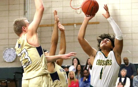 #1 Jahvon Myrthil of Holy Cross puts up a shot as #23 Max Mitchell of Notre Dame-Fairfield during CIAC Division 1 first round basketball action in Waterbury Monday. Steven Valenti Republican-American