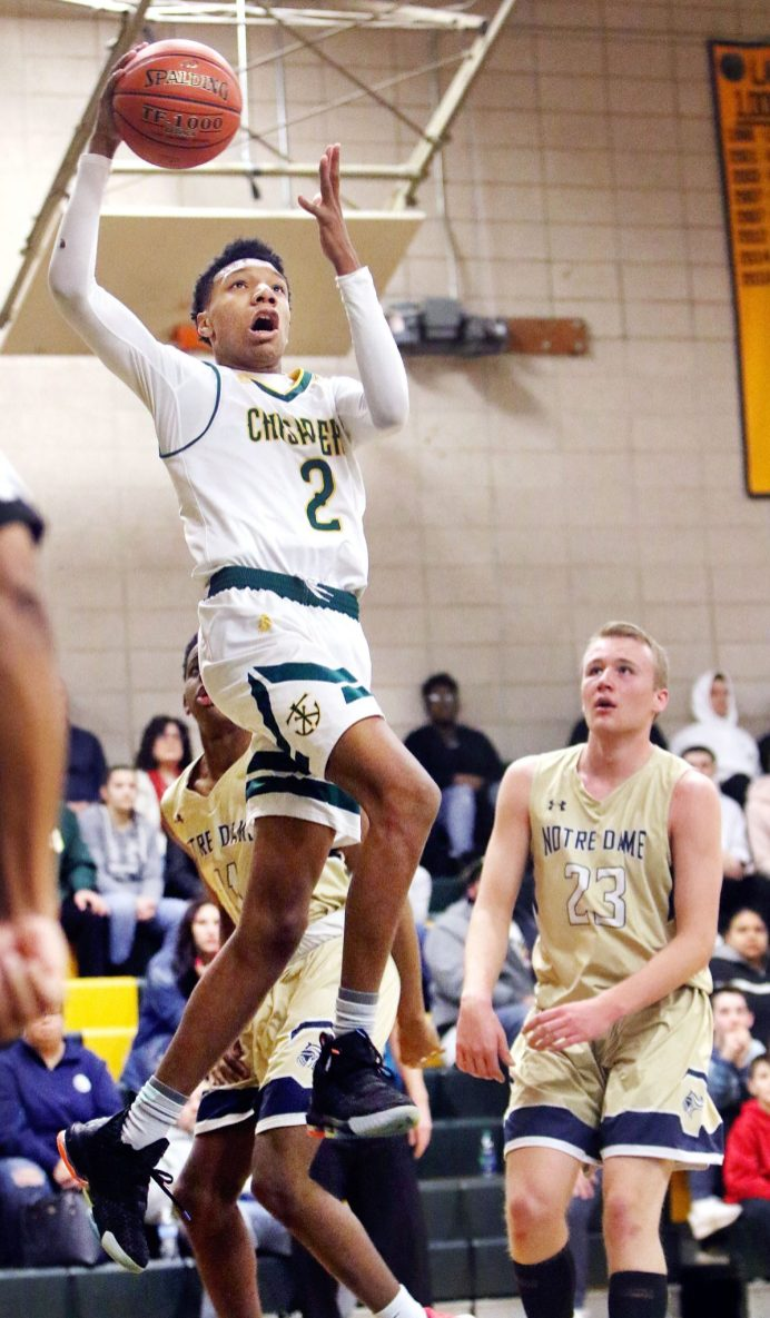 #2 Akili Evans of Holy Cross puts up a shot over #11 Blake Macklin, and #23 Max Mitchell of Notre Dame-Fairfield during CIAC Division 1 first round basketball action in Waterbury Monday. Steven Valenti Republican-American