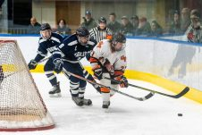 Watertown/Pomperaug's Jacob Oldham #21 gets to the puck in front of WMRP'S Ben Mroczka #8, behind the WMRP net, during a Division II Hockey quarterfinal game between WMRP and Watertown/Pomperaug at Trinity College in Hartford on Friday. Bill Shettle Republican-American