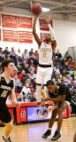 #2 Lorenzo Washington of Sacred Heart High launches a 3 pointer over #2 Mileeq Green of Trumbull High during the CIAC quarterfinal in Southbury Monday. Steven Valenti Republican-American