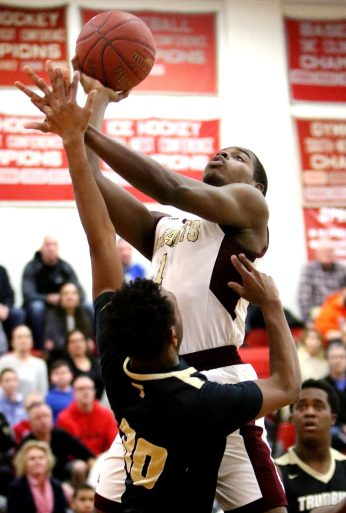 #1 Nate Tabor of Sacred Heart High puts up a shot over #30 Timmond Williams of Trumbull High during the CIAC quarterfinal in Southbury Monday. Steven Valenti Republican-American