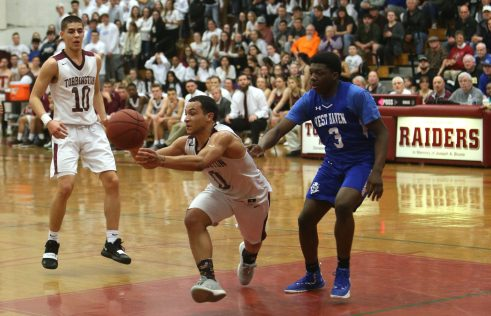 Torrington High School's Dontae Thomas passes the ball in front of teammate Joel Villanueva during the quarterfinals of the Division III boys varsity basketball tournament in Torrington against West Haven High School on Monday, March 11, 2019. Emily J. Reynolds. Republican-American
