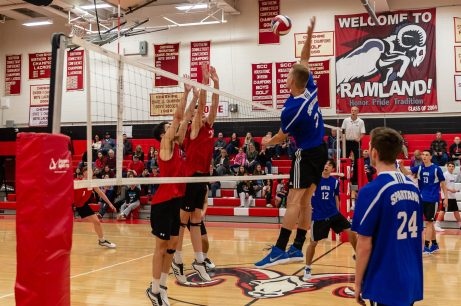 Lewis Mills' Josh Schibi #27, right, gets ready to spike the ball against Cheshire defenders Alex Irizarr 313, left, and Colby Hayes #25, during a boys volleyball match between Lewis Mills and Cheshire at Cheshire High School in Cheshire on Friday. Bill Shettle Republican-American