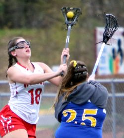 #18 Adriana Ferrucci of Wolcott High looks to pass against #25 Kaylyn Vogel of Housatonic Valley Regional High during Lacrosse action in Wolcott Thursday. Steven Valenti Republican-American